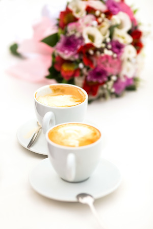 Two white cups of Cappuccino coffee with heart shaped milk foam photo