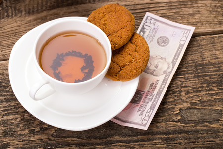 tea party: ivory tea cup with sweet cookie, and dollar money on wooden palette