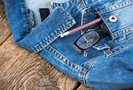 denim jacket: glasses and pencil in pocket of denim jacket on wooden  Stock Photo