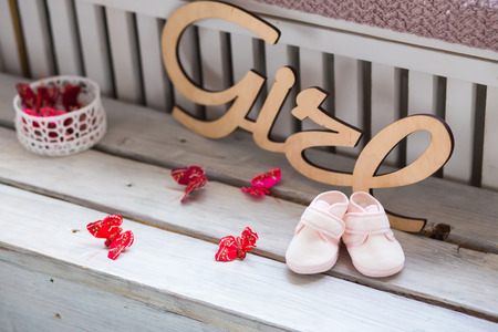 fancy girl: Sweet fancy and colorful baby shoes on the wooden desk with girl word