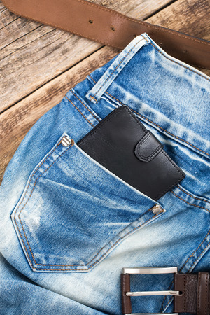 blue jeans pocket with Wallet black on wooden  photo
