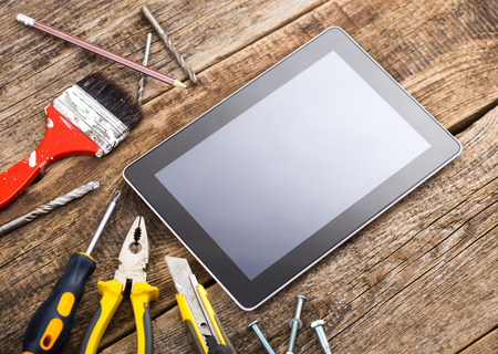 Different equipment tools of builder and tablet pc on wooden texture table Standard-Bild