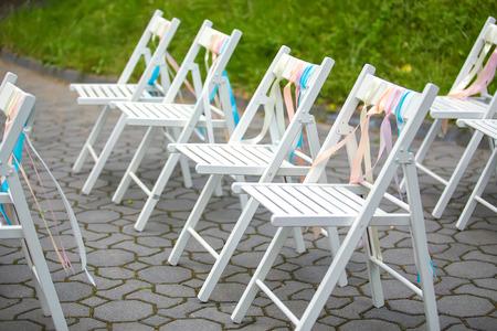 White wedding chairs decorated on ceremony Standard-Bild