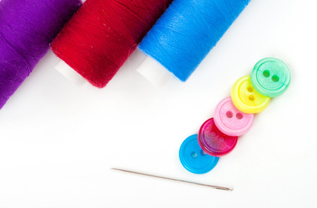 needle and thread: Needle, thread and buttons of different colors on white background