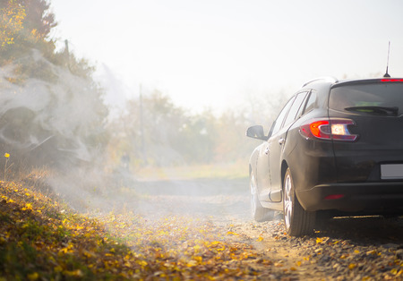 space weather tire: The car on old road near autumn park with fog Stock Photo