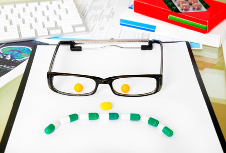 sad face with glasses from pills on doctors table photo