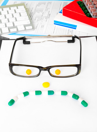 sad face sign with glasses from pills on doctors table photo