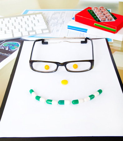 smile face with glasses from pills on doctors table photo