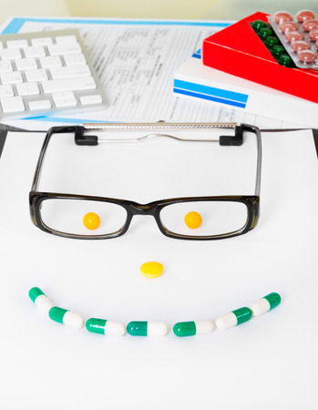 smile face sign with glasses from pills on doctors table photo