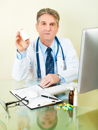 doctor with the tablet (pill, capsule) box, bottle in hand photo