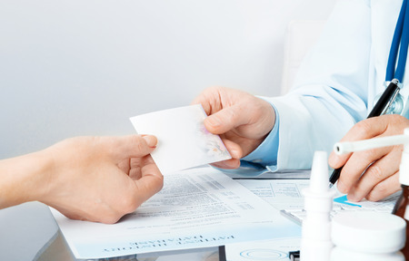 doctor giving pills: doctor at his workplace give a recipe to patient and write Stock Photo