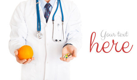 medical doctor with pills in one hand and orange in other isolated on white with your text Stock Photo