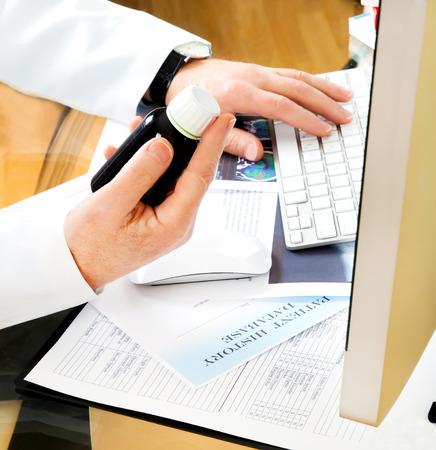 patient notes: Doctor using a computer to prepare an online prescription or writing patient notes from a medical examination
