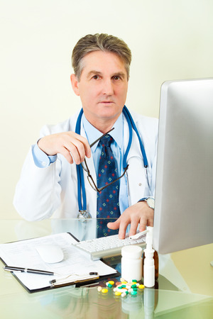 patient data: Smiling Doctor on his workplace with computer, pills, tablets, and patient data history