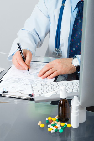 Doctor on his workplace with computer, pills, tablets, write a prescription patient data history photo