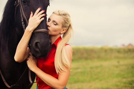 saturate: Young cute woman in saturate long dress with black strong and muscular horse in field