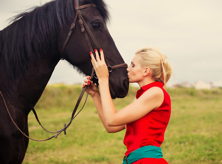 horse love horse kiss animal love: Young cute woman in saturate long dress with black strong and muscular horse in field