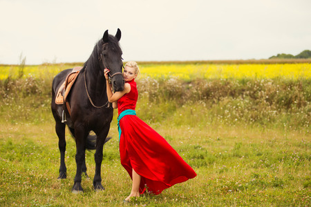 Young cute woman in saturate long dress with black strong and muscular horse in field photo
