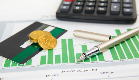 coin, a calculator, a pen and business card on the business papers photo