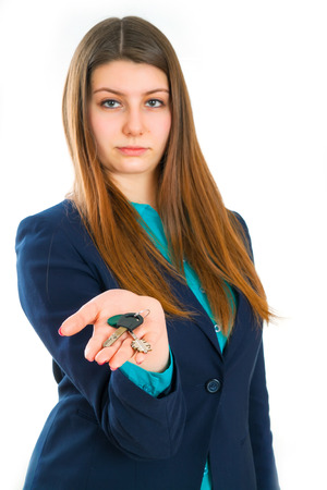 hand key: Attractive serious girl in a classic suit holding in her hand key. Isolated on white background