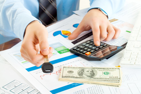 male manager giving key and account money on calculator photo