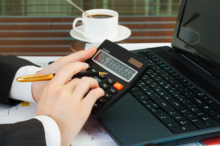 Accounting. Business woman at workplace with laptop and calculator photo