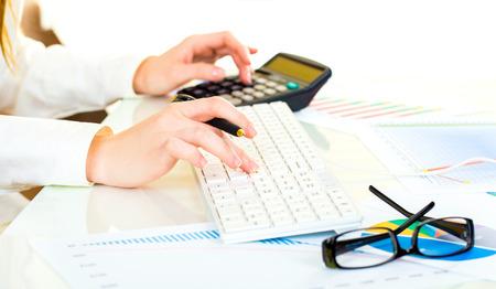 電卓とビジネス オフィスでキーボードに取り組んでいる美しい手を持つ女性