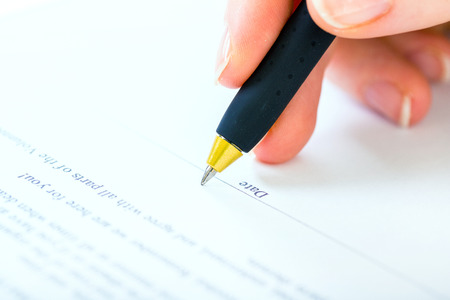 contractual: Woman at office desk signing a contract with shallow focus on signature.