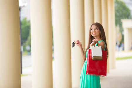 stunning and very beautiful woman in dress with long brown hair holding car key and colored shopping bags photo