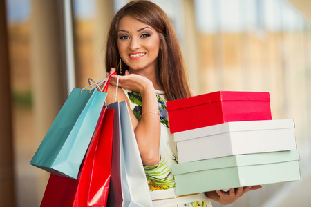stunning and very beautiful woman in dress with long brown hair with colored shopping bags photo
