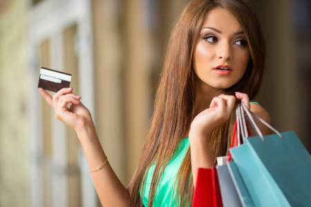 stunning and very beautiful woman in dress with long brown hair holding card and colored shopping bags photo