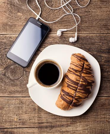 コーヒーとクロワッサンのスマート フォンとヘッドフォン 写真素材