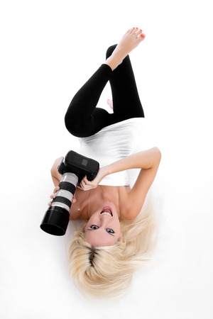shootting: Pretty young blonde smiling woman taking pictures on the unknown camera. Isolated over white.