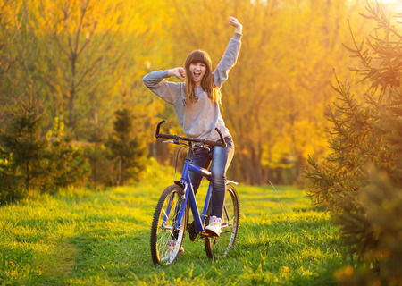Happy girl with arms outstretched over a bicycle and looking the view, in a green meadow at sunset