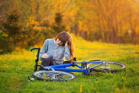 girl sitting down: Woman with pain in knee joints after biking on bicycle in park at sunset. Girl sitting down with painful face expression. Knee pain bike injury.