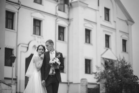 besos apasionados: Pares de la boda cerca de un antiguo edificio en blanco y negro Foto de archivo