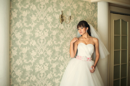 nude bride: Gorgeous bride in wedding dress in luxury interior with diamond jewelry posing at home and waiting for groom. Romantic rich happy girl in bridal dress Stock Photo