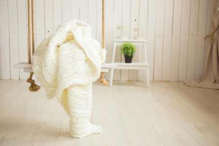 totter: Creamy sweater on wooden swing with rope Stock Photo