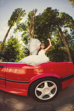 cabriolet: Runaway bride. Beautiful woman on red cabriolet Stock Photo