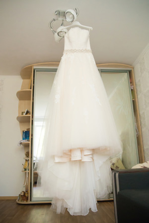 luster: wedding dress hanging on luster at hotel room Stock Photo