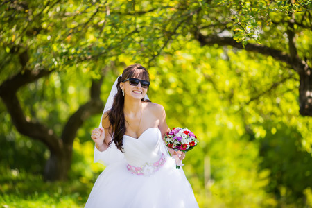 marriageable: Beautiful bride in sunglasses posing in park Stock Photo