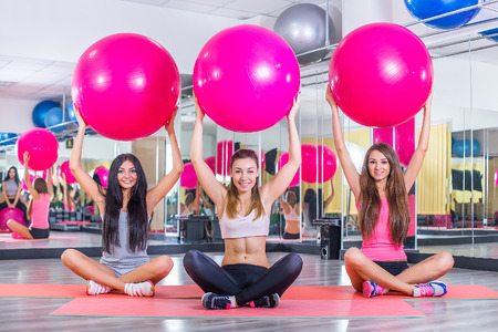 fitness: Fitness class holding up exercise balls in studio at the gym