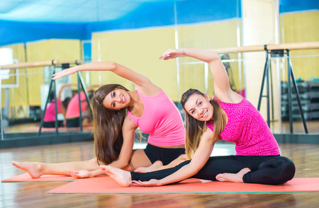 pilates studio: Class and instructor doing stretching pilate exercises in fitness studio Stock Photo