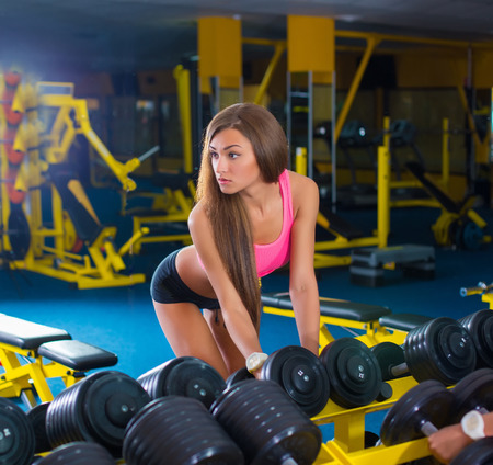 brunette sexy fitness girl in sport wear with perfect body in the gym posing