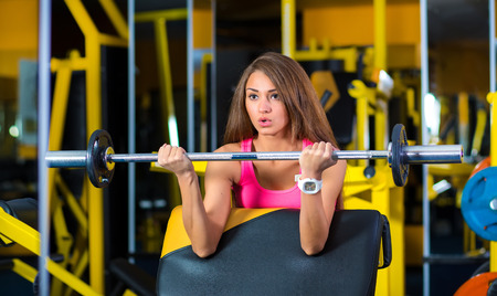 exhalation: Woman in gym lifting weights