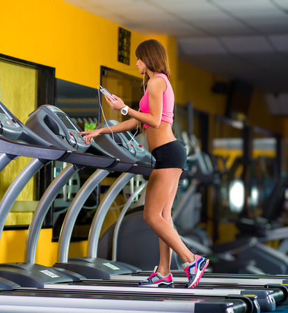 musculation: Smiling athletic woman training on a running machine with earphones in a fitness center