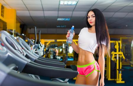Brunette woman with perfect body at a fitness club with bottle of fresh cold water photo