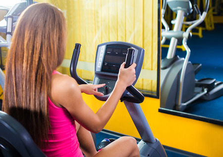 control panel: Girl with long hair press start button on bicycle in gym Stock Photo
