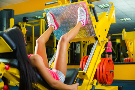 press: Side view of a fit young woman doing leg presses in the gym