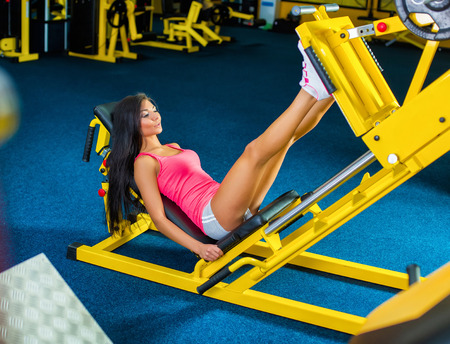 toning: Side view of a fit young woman doing leg presses in the gym